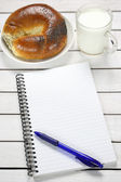 Notebook, croissant and milk on wooden table — Stock Photo
