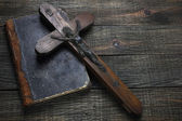 Cross and old book on wooden table — Stock Photo