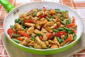 Fried chicken with vegetables in frying pan — Stock Photo