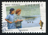 Boys with fishing pole and caught fish — Stockfoto