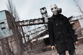 Man in gas mask standing at the factory after doomsday — Stock Photo