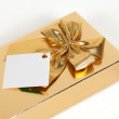 Stock Photo: Golden gift box with a bow on a white background