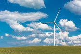 Wind farm on rural terrain with cloudy blue sky — Stock Photo