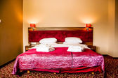 Double bed in luxury hotel room with towels and bathrobe — Stock Photo