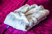 White bathrobe on the bed in hotel room — Stock Photo