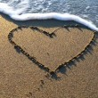 Heart drawn on the beach sand with sea foam and wave — Stock Video