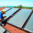 Stock Photo: Worker installs solar panels