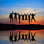 Silhouette of jumping friends — Stock Photo
