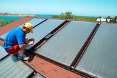 Worker installs solar panels  — Stock Photo