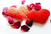 Rode harten en rozenblaadjes op de witte achtergrond — Stockfoto