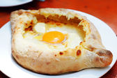 Ajarian or Adjaruli khachapuri, filled with cheese and topped wi — Stock Photo