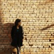 Beautiful woman and brick wall — Stock Photo
