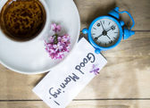 Cup of coffee and lilac flower — Stock Photo