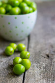 Green plums and daisy — Stock Photo