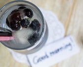 Blueberry juice with ice and flowers — Stock Photo