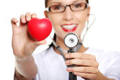 Female doctor holding red heart in hand — Stock Photo