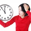 Shocked woman holding office clock — Stock Photo