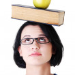 Student with an apple and book on her head - Stock Photo