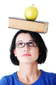 Student with an apple and book on her head — Photo