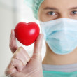 Male surgeon holding red heart — Stock Photo
