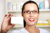 Female pharmacist with business card in pharmacy — Stock Photo