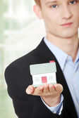 Young business man holding house model — Stock Photo