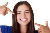 十几岁的女孩指着她完美的牙齿上 — 图库照片