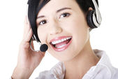 Young call-center assistant smiling at the camera — Stock Photo