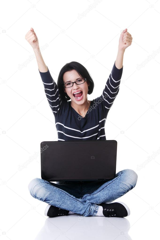Happy young woman with fists up using her laptop, isolated on white.  — Stock Photo #13266419