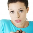 Beautiful woman with hand full of chocolates — Stock Photo