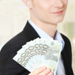 Young handsome businessman holding euros - Stock Photo
