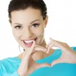 Attractiveyoung woman showing heart gesture — Stock Photo #16935987