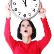 Shocked woman holding office clock - Lizenzfreies Foto