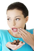 Embarrassment woman with chocolates — Stock Photo