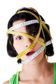 Beautiful young woman with measuring tape — Stock Photo