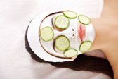 Young woman with cucumber slices on the face — Stock Photo