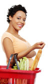 Pregnant woman with shopping basket — Stock Photo