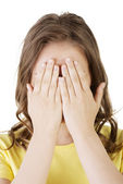 Genç teen kadın elleriyle yüzünü kaplayan — Stok fotoğraf