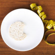 Biten waffle on plate next to measuring tape. — Stock Photo