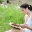 A beautiful young girl reading a book outdoor — Stock Video