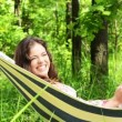 An attractive woman lying in a hammock with a tablet computer. — Stock Video