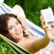 Young woman in a hammock in garden doing snapshot. — Stock Photo