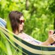 młoda kobieta leżący w hamaku w ogrodzie z e-book — Zdjęcie stockowe