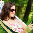 Young woman lying in a hammock in garden with E-Book. — Stock Photo