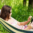 Young woman lying in a hammock in garden with E-Book. — Stock Photo #27555049