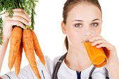 Female doctor holding healthy carrots. — Stock Photo