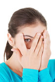 Shy teenage girl peeking through covered face — Stock Photo