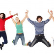 Group of happy young people jumping in the air — Stock Photo
