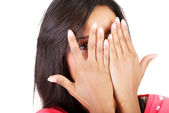 Shy woman peeking through covered face. — Stock Photo