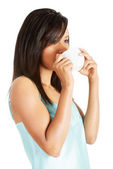 Attractive woman in nightwear drinking from cup — Stock Photo